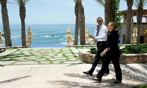 Clinton and Obama walk together after a 2012 meeting in Mexico.