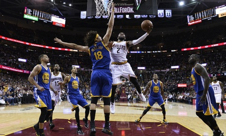Cleveland Cavaliers guard Kyrie Irving (2) drives against Golden State Warriors forward Anderson Varejao (18) during the second half of Game 3 of basketball's NBA Finals in Cleveland June 9.