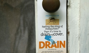 A flyer is left on the doorknob of a home by an inspector from the Miami-Dade County Mosquito Control department on Tuesday in Miami.