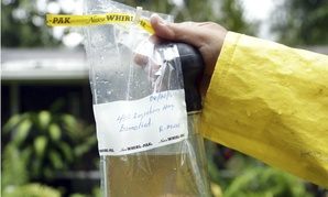 Robert Muxo of the Miami-Dade County Mosquito Control department, holds a sample of water that was standing in a potted bromeliad in Miami.
