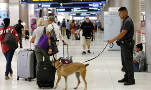 A K-9 handler with the Miami-Dade police department patrols at Miami International Airport Friday.