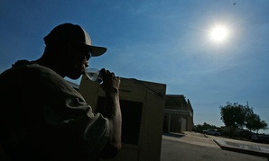 A staffer at the Phoenix Rescue Mission takes a drink of water. Temperatures reached over 115 degrees in Arizona in June.