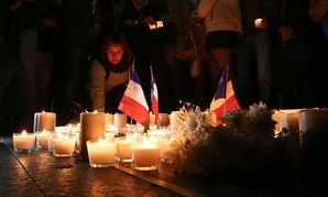 A woman places a candle during a vigil to honor victims of the Bastille Day tragedy in Nice, France, in Sydney, Australia on Friday.