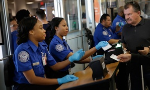 Transportation Security Administration employees check passengers' identifications at a security check point at LaGuardia Airport in May.