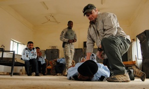 A contractor demonstrates a restraining technique during a training session for the Iraqi police in 2008.