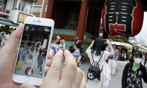"""A man tries to catch a Pikachu, a Pokemon character, while he plays """"Pokemon Go"""" in front of Kaminarimon, or Thunder Gate, at the Sensoji temple in Tokyo."""