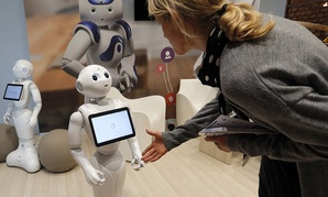 Engineer consultant Valerie Hawley, right, tries to shake hands with Pepper the robot of Softbank Robotics Europe.