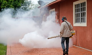 A Miami-Dade County mosquito control worker sprays around a home in the Wynwood area of Miami on Aug. 1.