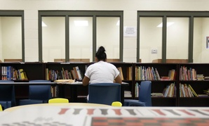 A woman uses the library at a temporary home for immigrant women and children detained at the border, in Karnes City, Texas.