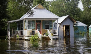 Floodwaters reach the front steps of a home near Holden, Louisiana.