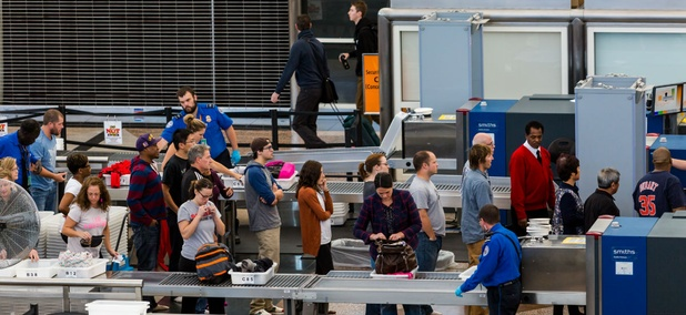 TSA officers inspect luggage at Denver International Airport.