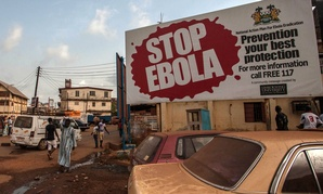 People pass a banner reading 'STOP EBOLA' forming part of Sierra Leone's Ebola free campaign in the city of Freetown, Sierra Leone, Friday, Jan. 15, 2016.