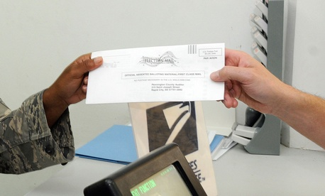 A postal clerk with the 379th Expeditionary Communications Squadron, receives a completed absentee ballot to be mailed Oct. 3, 2008, at an undisclosed air base in Southwest Asia.