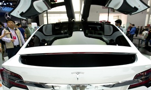A visitor looks at a Tesla Model X on display at the Beijing International Automotive Exhibition.
