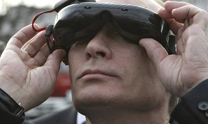 Russian Prime Minister Vladimir Putin tests goggles with an electronic connection that allows him to see the view from an unmanned drone aircraft.
