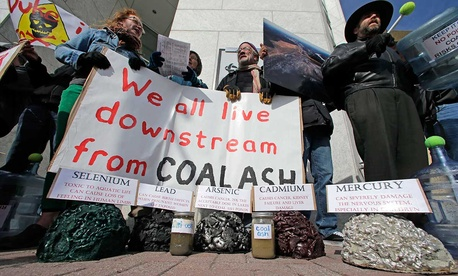 Demonstrators chant and hold signs behind a display of coal ash and the chemicals in it during a protest near Duke Energy's headquarters in Charlotte in 2014.