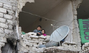Children peer from a partially destroyed home in Aleppo, Syria in February.