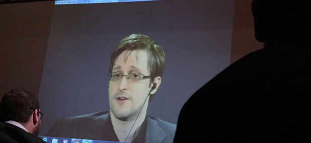 Former National Security Agency contractor Edward Snowden, center speaks via video conference to people in the Johns Hopkins University auditorium, in Baltimore in February.