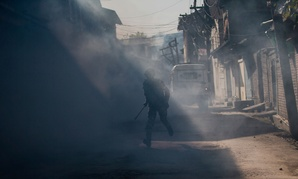 An Indian paramilitary soldier runs for cover amid tear gas smoke as Kashmiri protesters throw stones and bricks at him during a protest in Srinagar, Indian controlled Kashmir on Friday.