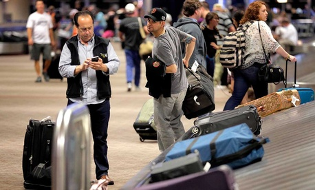 Passengers retrieve their luggage after their flights, Friday, May 27, 2016 at Sky Harbor International Airport in Phoenix.