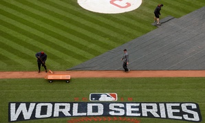 Members of the grounds crew prepare the field for batting practice for baseball's upcoming World Series