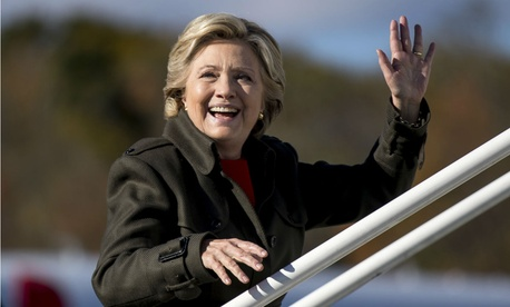 Hillary Clinton waves to members of the media as she boards her campaign plane at Westchester County Airport in White Plains, N.Y., Oct. 31.