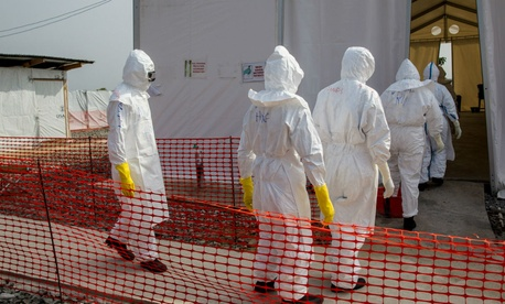Nurses enter an Ebola treatment unit in Liberia. The facility is operated by the International Organization for Migration in partnership with Liberia's Ministry of Health and Social Welfare and supported by USAID's Office of U.S Foreign Disaster.