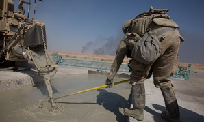 An airman assigned to the 1st Expeditionary Civil Engineering Group levels poured concrete in a trench during runway repair operations at Qayyarah West airfield, Iraq, Oct. 8, 2017.