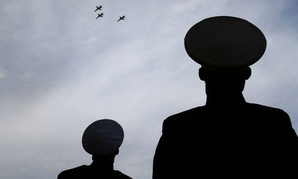 Marine Cap. Lawrence Seilert, left, and Staff Sgt. David Harper watch jets flying the missing man formation aerial salute during a Veteran's Day parade in Dallas.