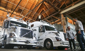 Employees stand next to self-driving, big-rig trucks during a demonstration at the Otto headquarters, in San Francisco.