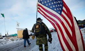 Navy veteran Rob McHaney walks with an American flag at the Oceti Sakowin camp where people have gathered to protest the Dakota Access oil pipeline in Cannon Ball, N.D., on Sunday.