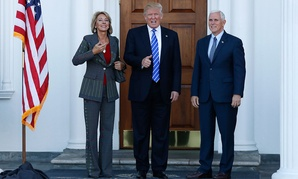 Donald Trump calls out to media as he Vice President-elect Mike Pence and Betsy DeVos pose for photographs in New Jersey in November.