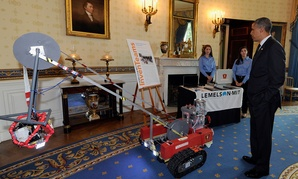 Barack Obama looks over a remotely operated vehicle to help firefighters with ice search and rescue calls developed by Olivia Van Amsterdam, left, and Katelyn Sweeney, center, at the White House Science Fair in 2014.
