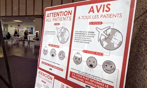 A sign advising advising those who are showing possible Ebola symptoms is posted in a lobby of New York's Bellevue Hospital in 2014.
