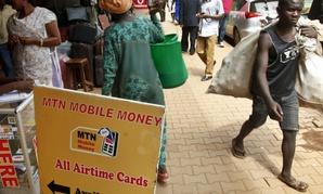 Pedestrians walk past a mobile money point in Kampala, Uganda.