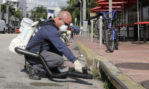"""Miami-Dade mosquito control inspector Yasser """"Jazz"""" Compagines sprays a chemical mist into a storm drain, Tuesday, Aug. 23, 2016, in Miami Beach, Fla."""