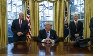 Vice President Mike Pence, left, and National Trade Council adviser Peter Navarro, right, wait for President Donald Trump to sign executive orders on Monday.