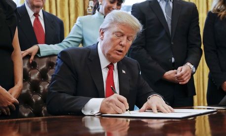 Trump signs the executive order to cut regulations on Monday.
