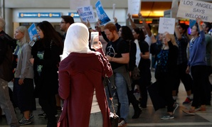 A traveler records demonstrators as they march through Tom Bradley International Terminal as protests against President Donald Trump's executive order banning travel from seven Muslim-majority countries continue at Los Angeles International Airport Sunday