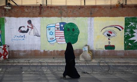 A woman walks past anti-Saudi and U.S. graffiti sprayed on a wall of the closed Saudi embassy in Sanaa, Yemen in 2015.