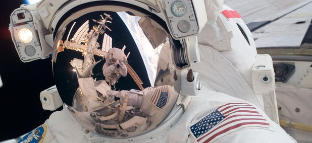 STS-124 Mission Specialist Mike Fossum participates in the mission's first spacewalk. Visible in the reflections of his helmet visor are various components of the station, Earth's horizon and astronaut Ron Garan.