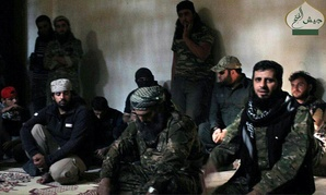 In this photo posted Oct. 30, 2016, by the Syrian militant group Ahrar al-Sham, shows the general commander of Ahrar al-sham, Mohannad al-Masri, center, visiting fighters in rural western Aleppo, Syria.