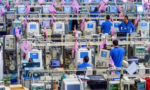 Factory workers assemble medical devices.