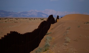 A CBP vehicle drives along the U.S.-Mexico border fence near Yuma, Arizona in 2010.