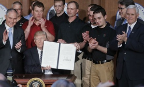 Trump signs the executive order at the EPA.