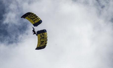"""Members of the U.S. Navy Parachute Team """"The Leap Frogs"""" perform a side plane during a skydiving demonstration above Mary G. Montgomery High School in Alabama in February."""