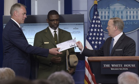 White House press secretary Sean Spicer (right) holds up the check Trump is giving to the National Park Service.