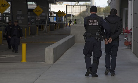 A Customs and Border Protection officer escorts a detainee to a processing area in March 2016.