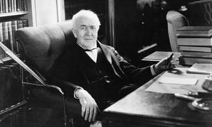 Thomas Edison sits at his desk.