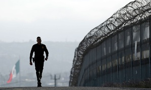 A CBP agent walks along the border fence in 2015 near San Diego.